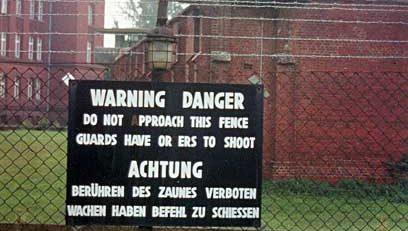 Сторожевая вышка на тюремной стене и предупредительная надпись на двух языках